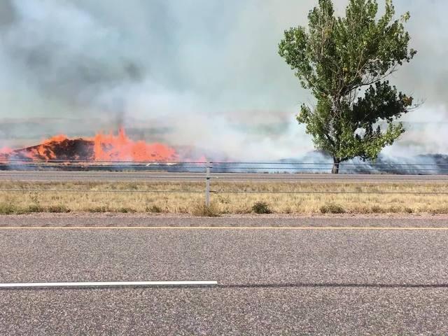 Grass fires burn just feet from major roadway