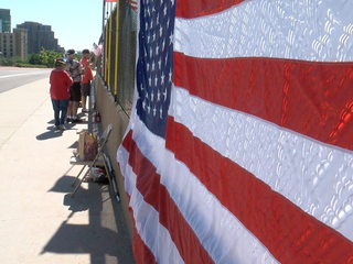 Patriotic group waves flags over I-25