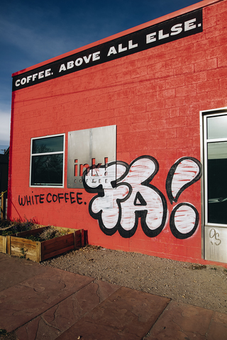 The Red Walls Of The Shop Are Now Decorated With The Words White Coffee In All Black Caps Along With Gentrify Deez Nuts Written On The Shops Sign