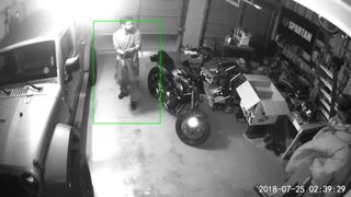Suspect caught on camera crawling into garage